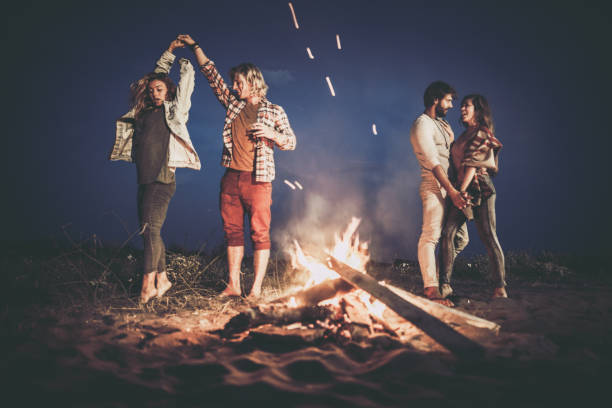 two happy couples dancing on a night party by the campfire. - falò spiaggia foto e immagini stock