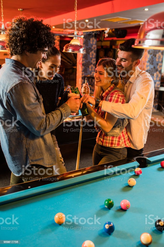 Cheerful couples enjoying while toasting with beer in a pool hall.