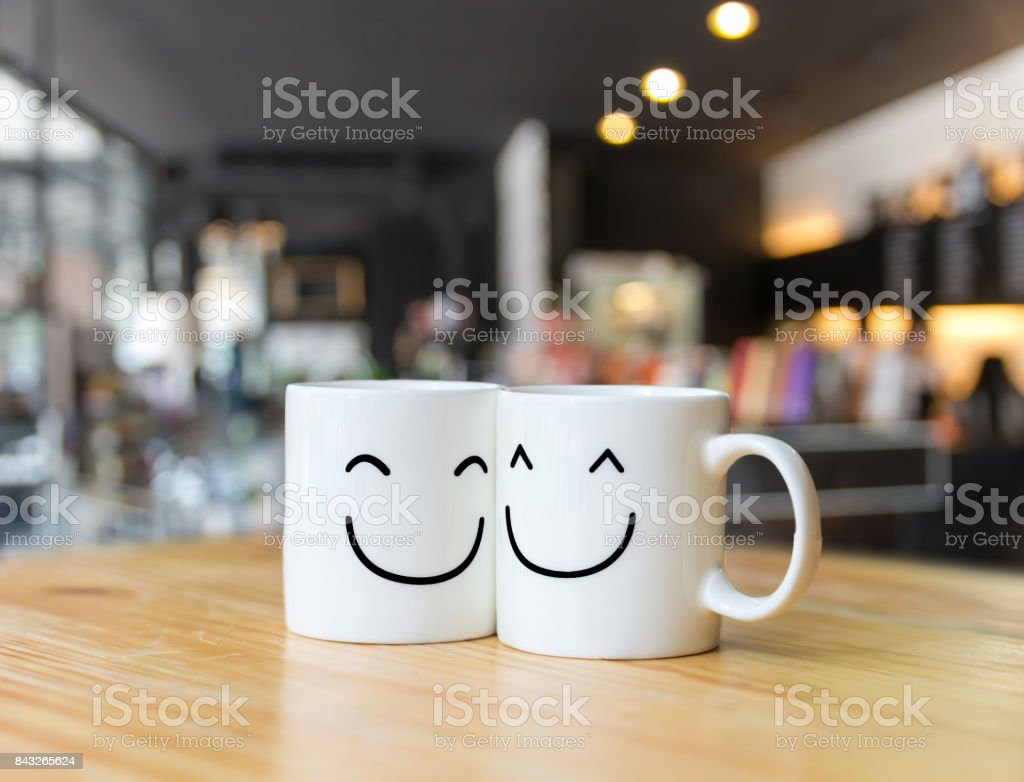 Two happy cups on coffee store blur background, Valentine lover concept stock photo