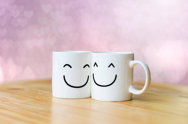 two happy cups on wood table with valentine's day hearts bokeh background - smiley face stock photos and pictures