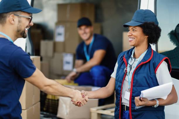 two happy delivery workers shaking hands outdoors. - postal worker стоковые фото и изображения