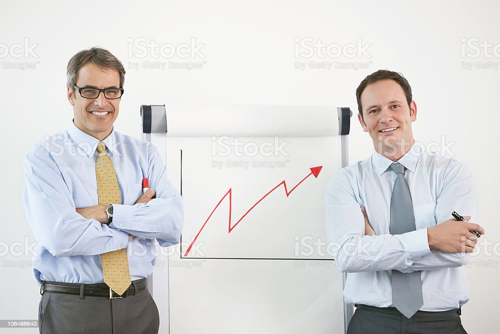 Two happy executives with line graph on Whiteboard, Flipchart representing business growth royalty-free stock photo