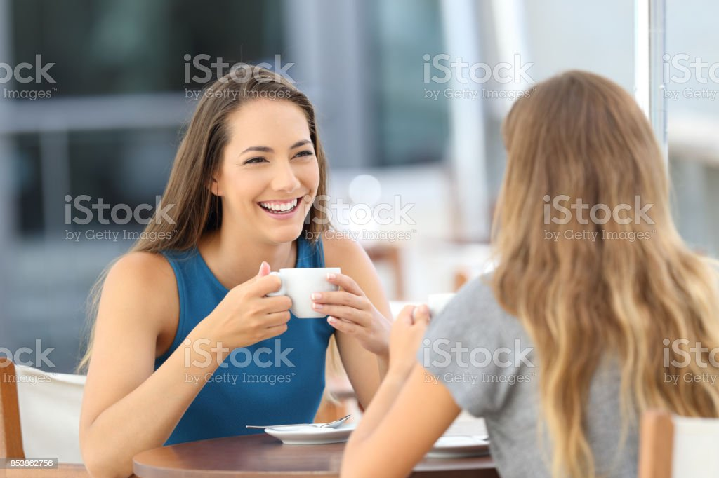 Two happy friends having a casual conversation stock photo