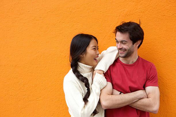 dois amigos felizes rindo contra fundo laranja - lifestyle color background - fotografias e filmes do acervo