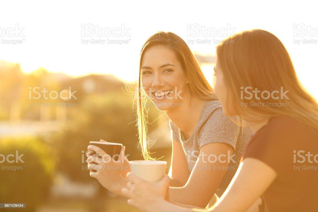 Zwei glückliche Freunde sprechen in einem Balkon bei Sonnenuntergang Lizenzfreies stock-foto