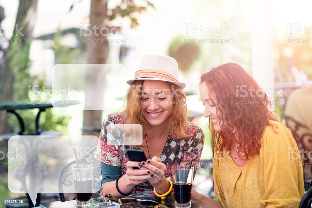 Two happy friends texting in a cafe stock photo