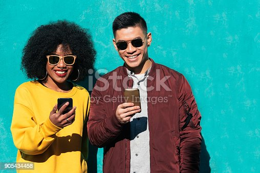istock Two happy friends using the mobile in the street. 905434458