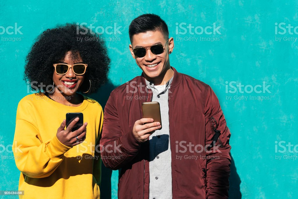 Two happy friends using the mobile in the street. stock photo