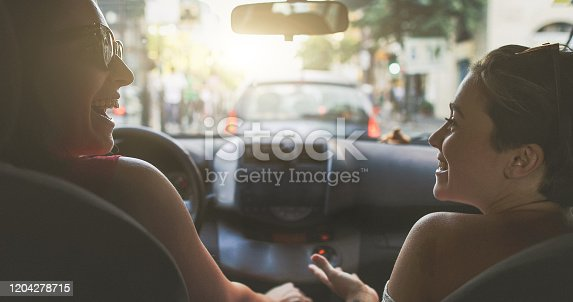 907987862 istock photo Two happy girl friends driving inside a car in the traffic of Rome, Italy 1204278715