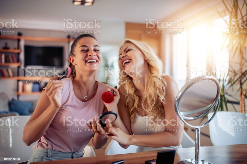 Two happy girls applying make up at home stock photo