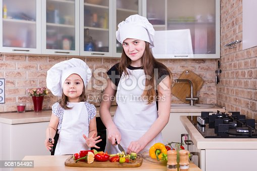 488109116istockphoto two happy girls cooking on kitchen 508154492