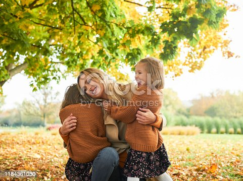 Two happy girls embracing their mommy