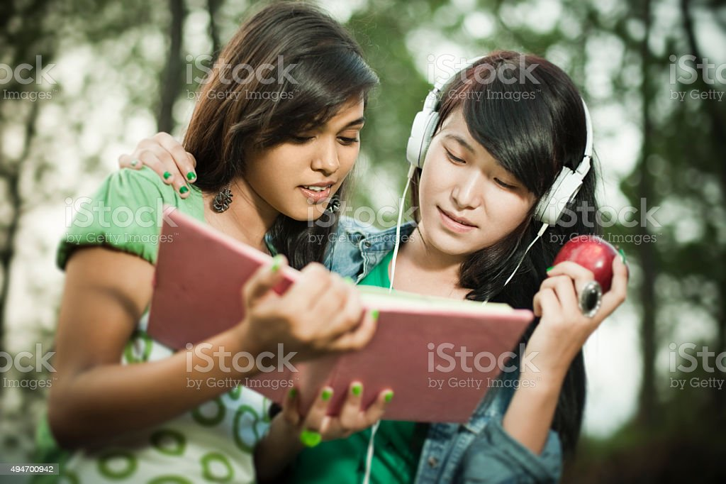 Outdoor day time image of two happy teenage friends of different...