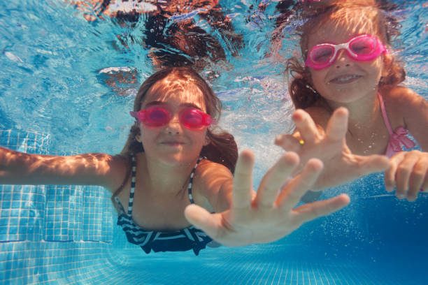 two happy girls in goggles swimming under water - swim arms imagens e fotografias de stock
