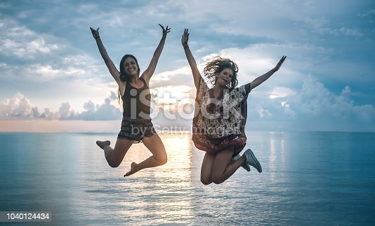 700603062istockphoto Two happy girls jumping at sunset on tropical beach 1040124434