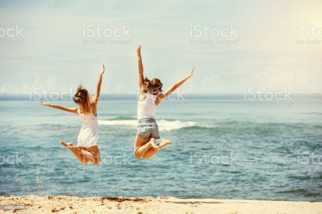 Two happy girls jumps at sunny beach royalty-free stock photo