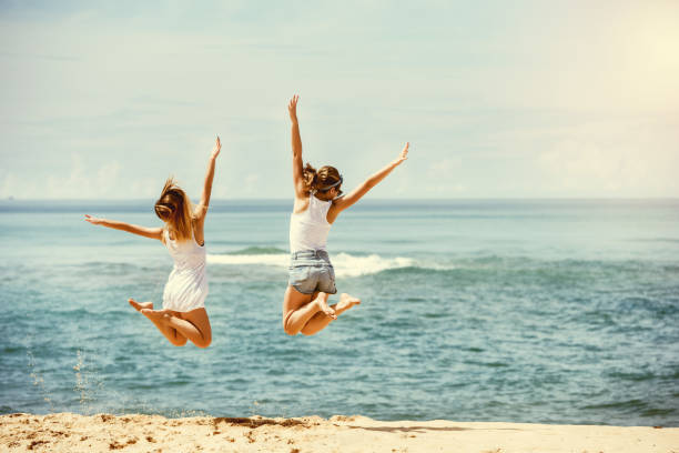 Two happy girls jumps at sunny beach stock photo