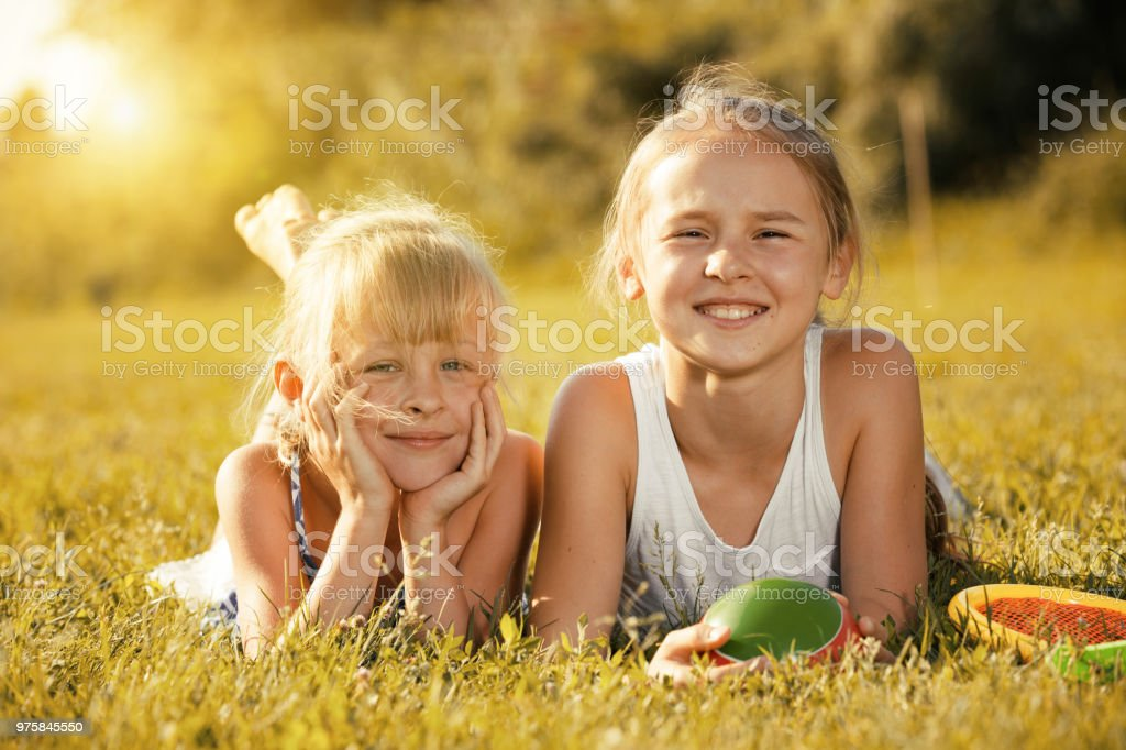Zwei glückliche Mädchen Verlegung auf Rasen - Lizenzfrei 8-9 Jahre Stock-Foto