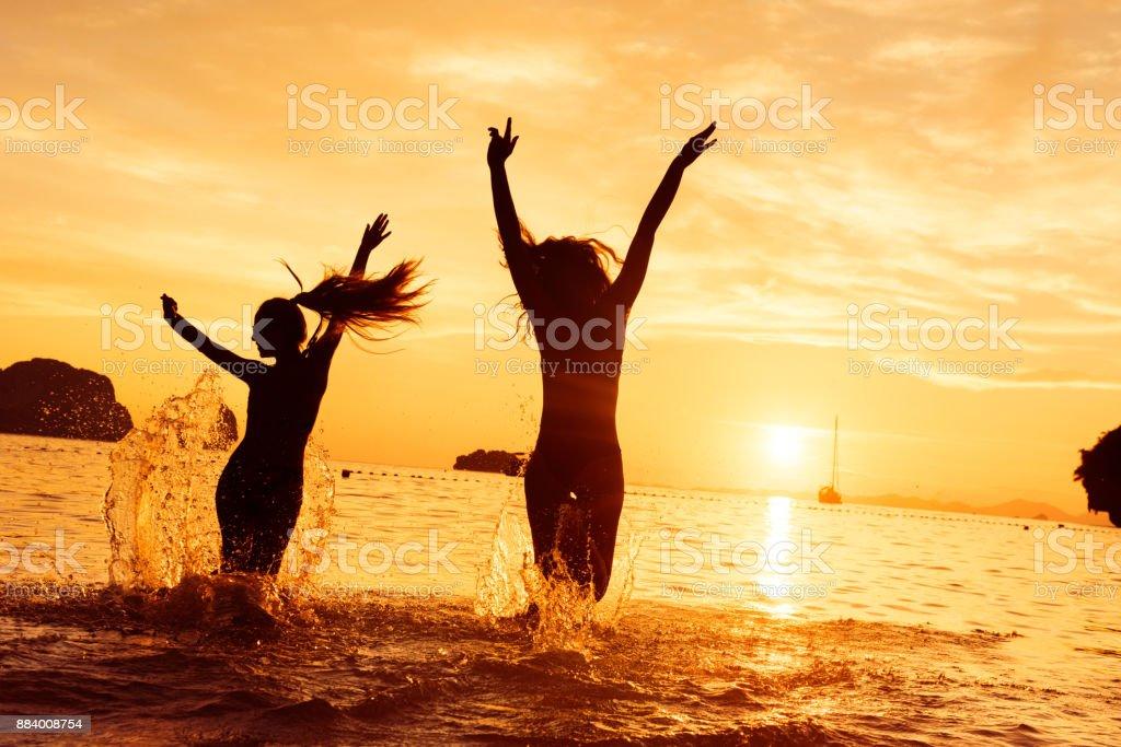 Dos chicas felizes corre al mar al atardecer - foto de stock