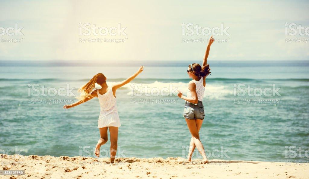 Diversión de playa de mar de dos niñas felices - foto de stock