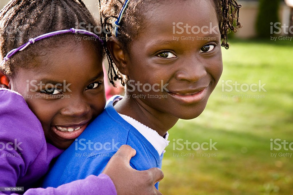 Two Happy Girls Smiling and Hugging Outside royalty-free stock photo