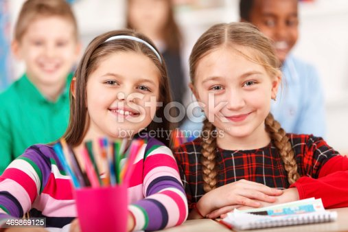 818512928istockphoto Two Happy Girls Smiling Together In The Classroom 469869125
