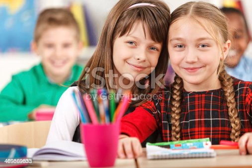 818512928istockphoto Two Happy Girls Smiling Together In The Classroom 469869833