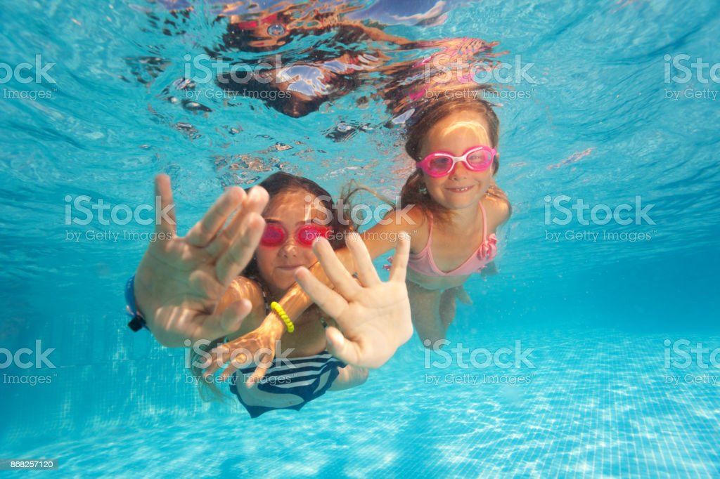Two happy girls swimming under clear water of pool stock photo
