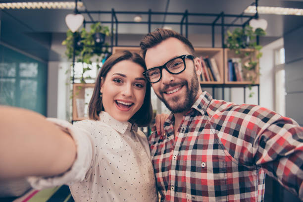 zwei glückliche lachende kollegen selfie während pause machen - lachmeister stock-fotos und bilder