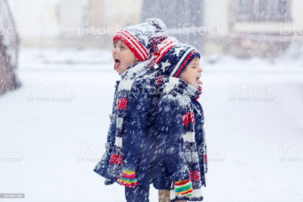 Two happy little boys having fun with snow in winter stock photo