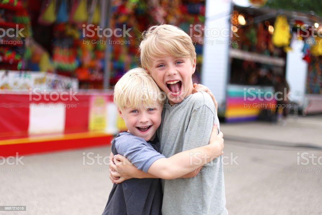 Two Happy Little Boys Hugging and Smiling at Small Town American Carnival stock photo