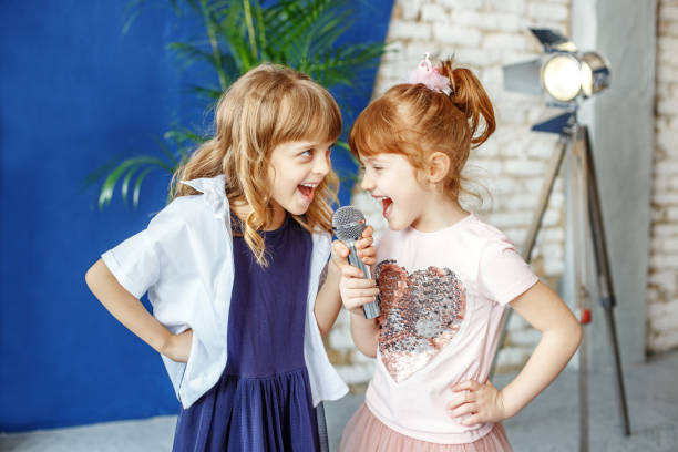 Two happy little children sing a song in karaoke. The concept is Two happy little children sing a song in karaoke. The concept is childhood, lifestyle, music, singing, friendship. singing stock pictures, royalty-free photos & images