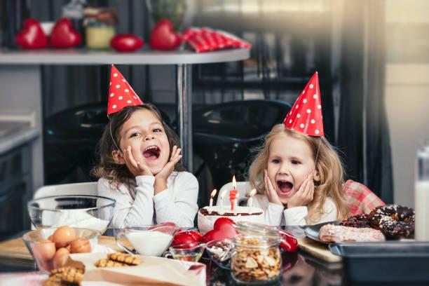 zwei glückliche kleine mädchen kind feiern einen geburtstag mit kuchen am tisch ist lieblich und schön - kinderzimmer tischleuchten stock-fotos und bilder