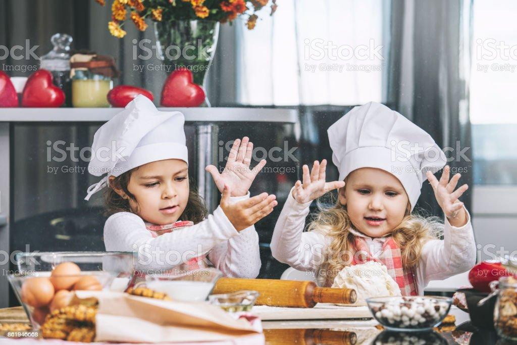 Dos niñas felizes niño cocinar con harina y masa en la mesa de la cocina es encantador y hermoso - foto de stock