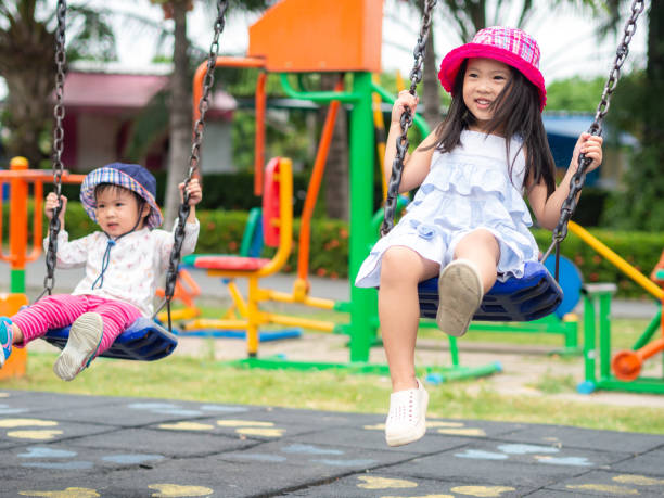 two happy little girls playing swing at the playground. happy, family, sister concept. - balouço imagens e fotografias de stock