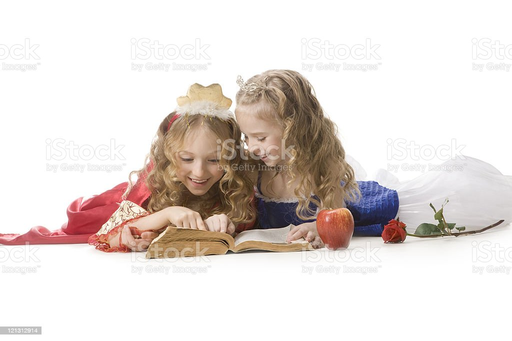 Two happy little  princesses reading a magic book .XXXL royalty-free stock photo