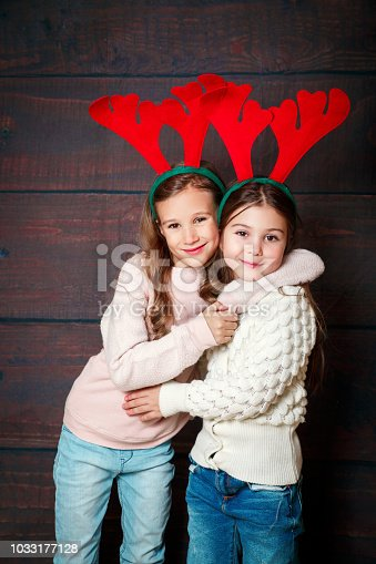 1062609644 istock photo Two happy little smiling girls embracing .Christmas concept. Smiling funny sisters in deer horns in studio. 1033177128