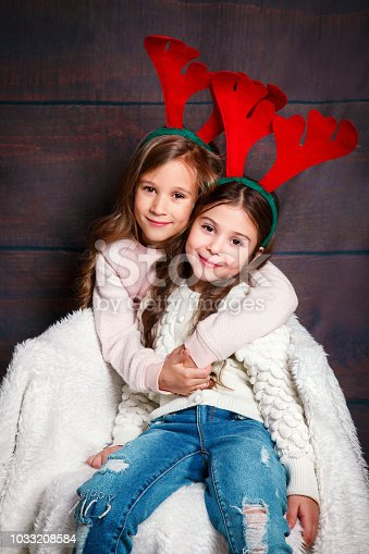 1062609644 istock photo Two happy little smiling girls embracing .Christmas concept. Smiling funny sisters in deer horns in studio. 1033208584