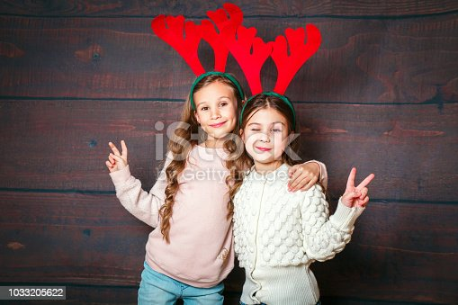 1062609644 istock photo Two happy little smiling girls having fun .Christmas concept. Smiling funny sisters in deer horns on wooden background 1033205622