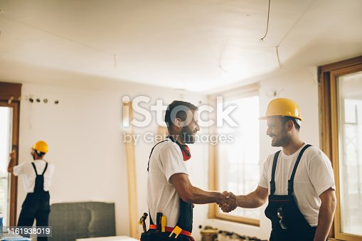 961745166istockphoto Two happy manual workers handshaking at construction site. 1161938019