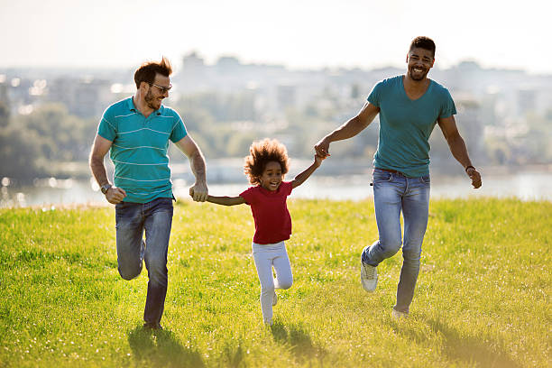 Two happy men running with African American little girl outdoors. stock photo