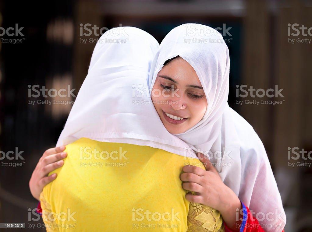 Deux femmes musulmanes heureux embrassant mutuellement sur l'Aïd. - Photo