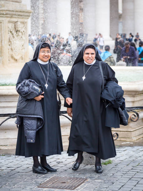 Two happy nuns posing for photo in front of the fountain