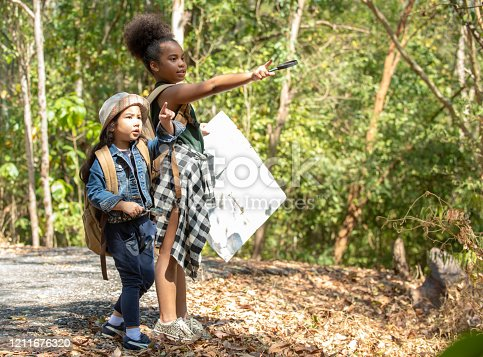 istock Two happy pretty child girls holding hands and hiking together with backpack and map in forest mountain. Kids having fun adventure walking in summer day. Children summer leisure activity concept. 1211676320