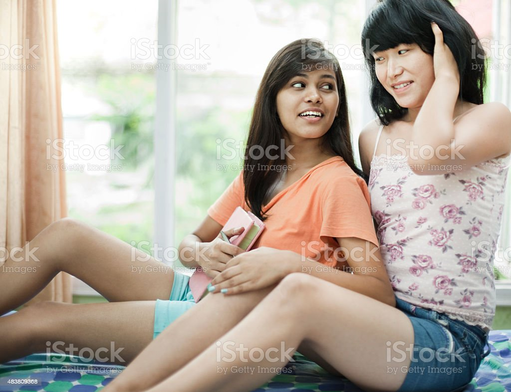 Indoor day time image shot in dorm room near window of two happy...