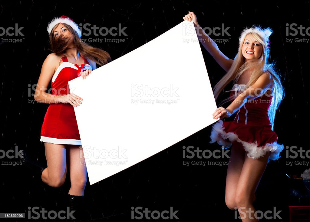 Two happy santa girls holding sign stock photo