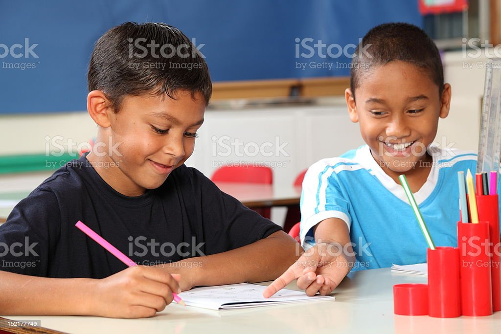 Two happy school boys enjoying and sharing learning in class royalty-free stock photo
