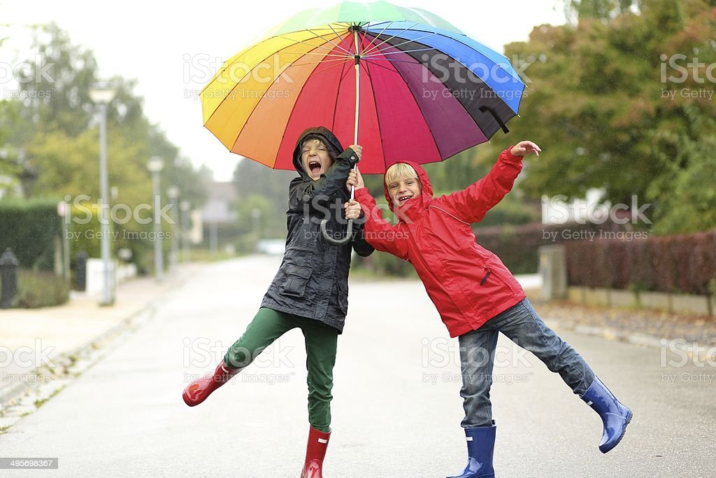 Two happy school boys sharing colorful umbrella stock photo