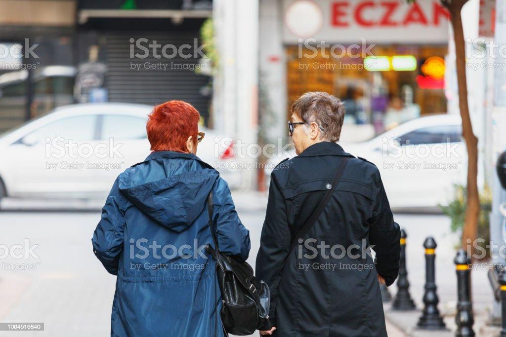 Two happy senior women on a walking street stock photo