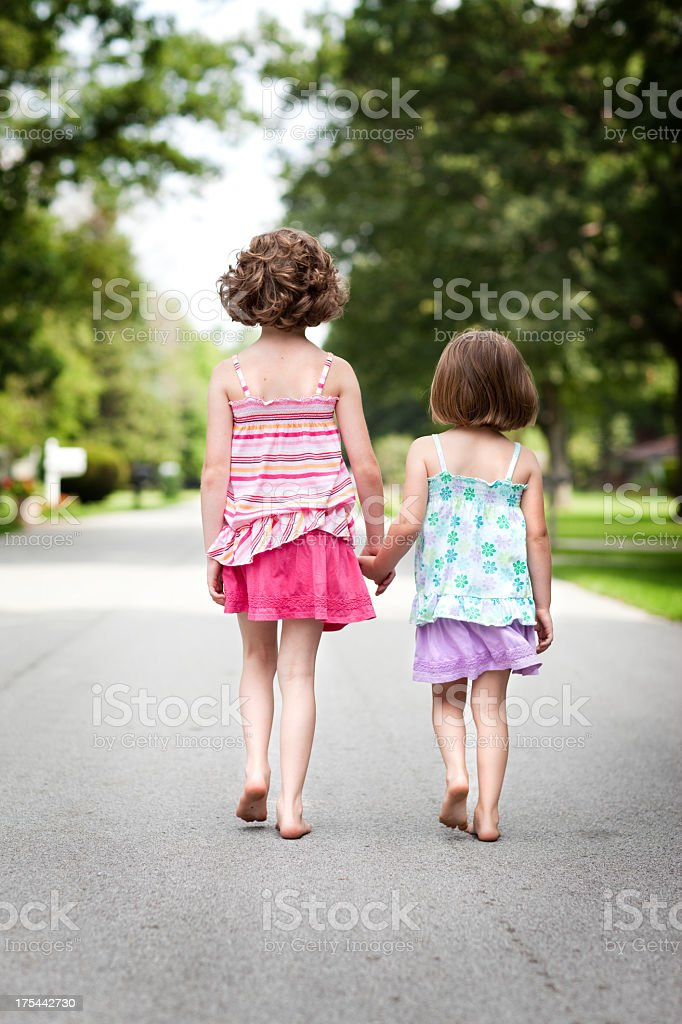 Two Happy Sisters Holding Hands and Walking Outside stock photo